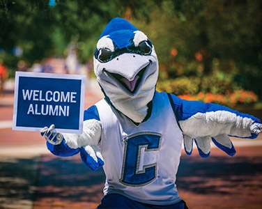 Billy Bluejay holding a Welcome Alumni sign on Creighton campus
