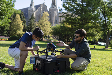 student and instructor working with a drone on Creighton campus
