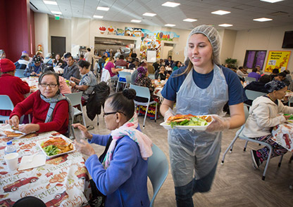 A student serves food at a community center