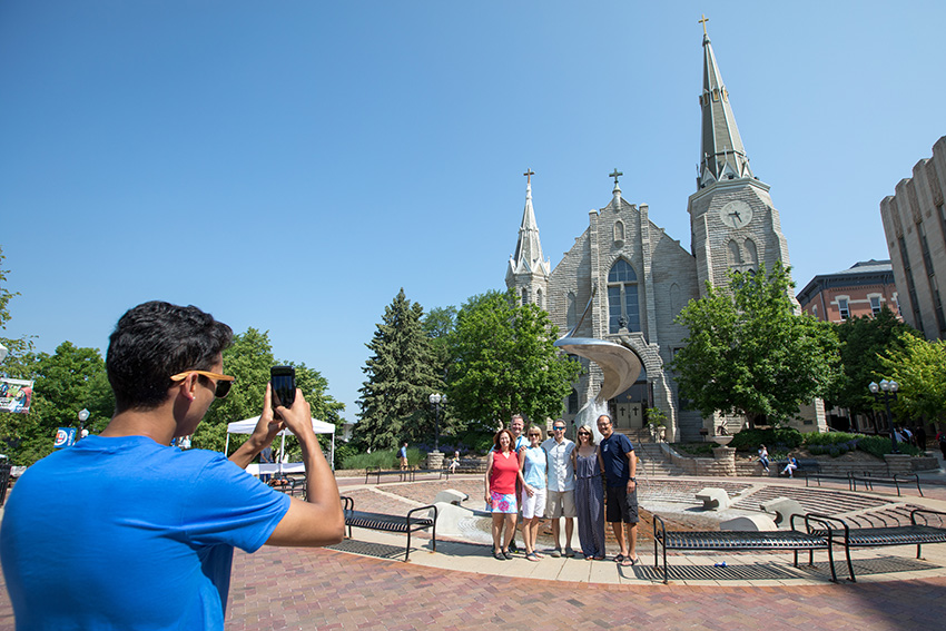 Creighton student takes a photo of a group of alumni in front of St. John's