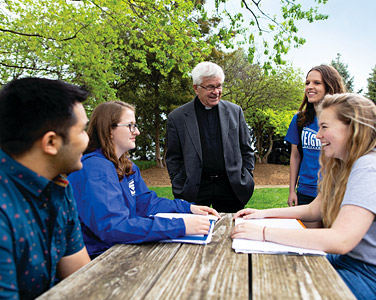 Jesuit and students talk in the Jesuit gardens