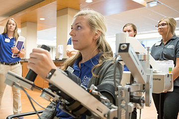 An OT student demonstrates assistive tech while her class watches.