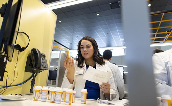 A pharmacy student cross-checks a prescription.