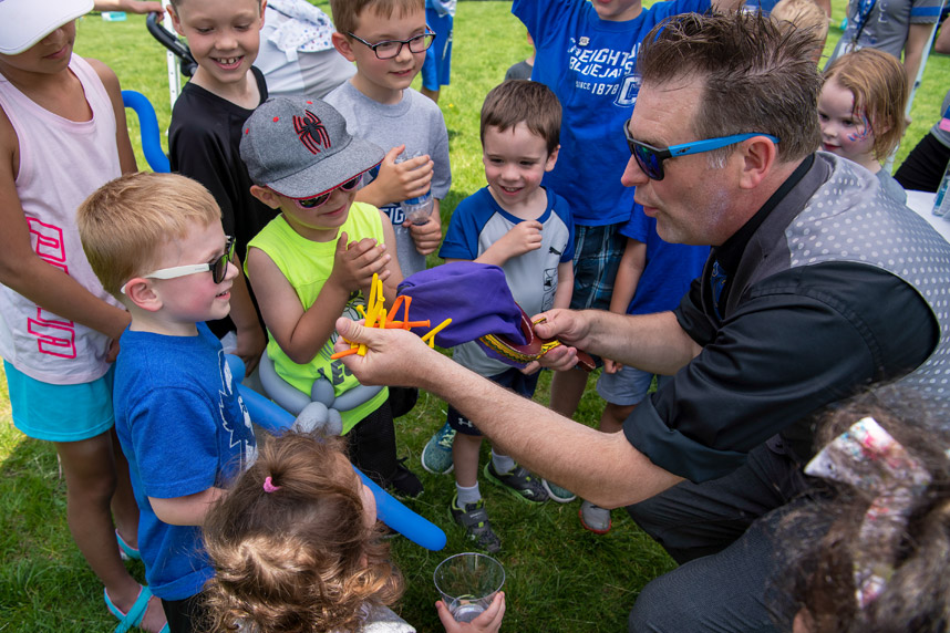 Creighton University reunion weekend man making balloon animals for children