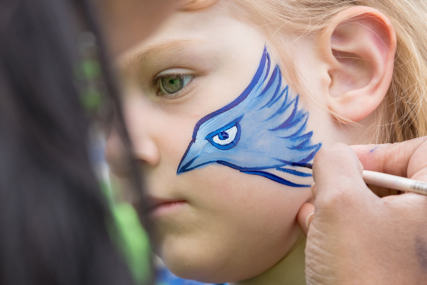 Child getting his face painted with a Bluejay