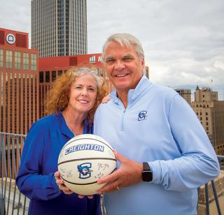 Creighton alum who support the champions circle smiling and holding a Creighton University basketball