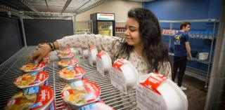 A student arranges food items at the Creighton Cupboard.
