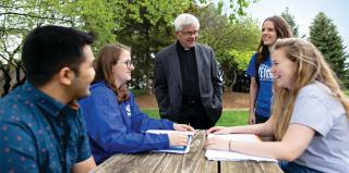 A Jesuit speaks with students at Creighton.