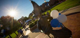 Billy Bluejay statue with blue and white balloons and Creighton campus in the background