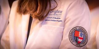 Female student wearing physician assistant white coat with Creighton seal