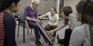 Students work with a patient on physical therapy.