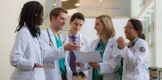 Three female and two male medical students huddle together to look at document