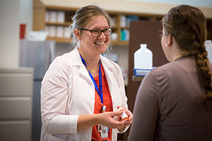 A pharmacy student speaks with a patient.